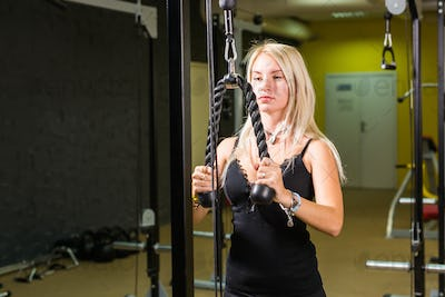 beautiful muscular fit woman exercising building muscles in gym