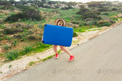 Young woman with blue suitcase making funny faces outdoors