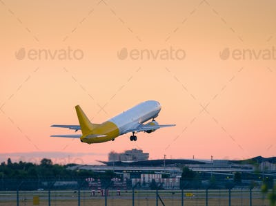 Taking off airplane from the runwayat sunset