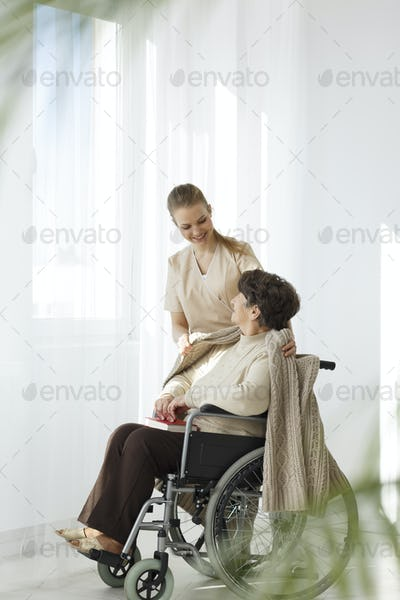 Nurse covering lady with blanket