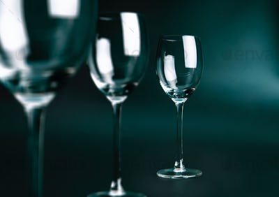 Three empty glasses on dark green background