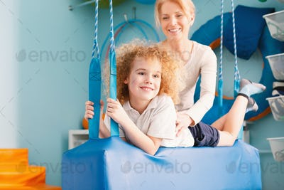 Boy laying on therapy swing
