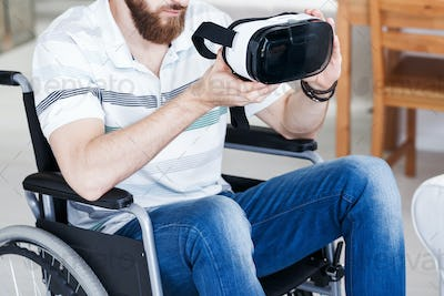 Disabled man holding VR goggles