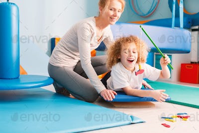 Kid playing with physiotherapist