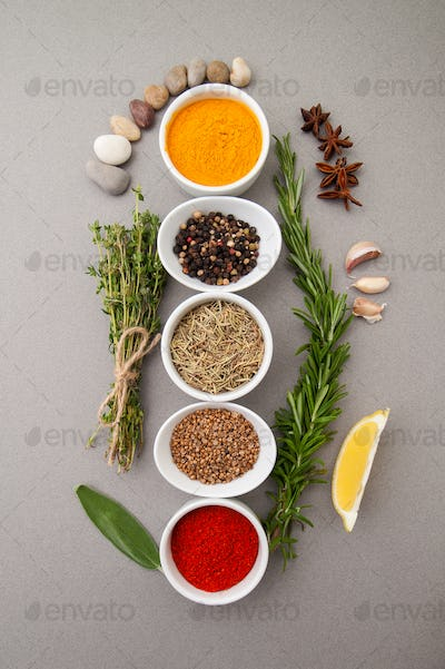 Various spices on a gray background.