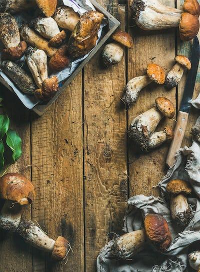 Freshly picked white forest mushrooms, leaves, knife on wooden background