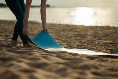 Attractive young woman folding green yoga or fitness mat after working out at the beach.