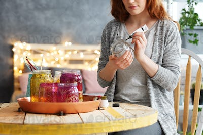 Woman painting jar at home