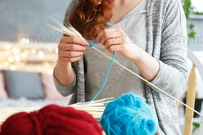 Woman making yarn decorations