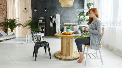 Woman drinking tea in apartment