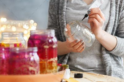 Woman decorating jars