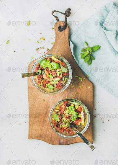 Healthy salad with quionoa, avocado, dried tomatoes, top view