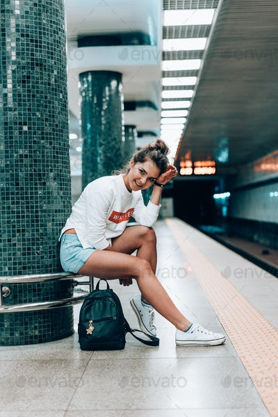 Beautiful young girl posing on metro station