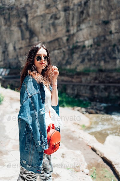 Girl standing near a rock wall