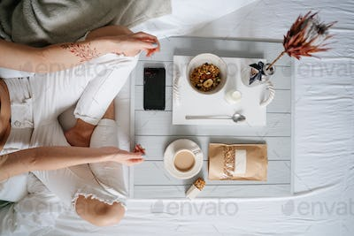 Woman eating cereals in bed
