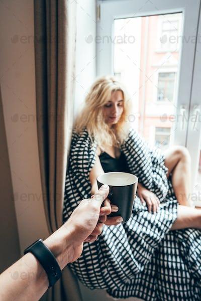 girl sitting on a window in a blanket