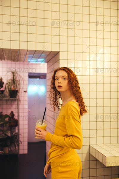 Concentrated young redhead curly lady standing in cafe