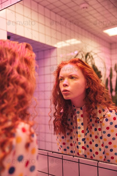 Concentrated young redhead curly lady looking at mirror.