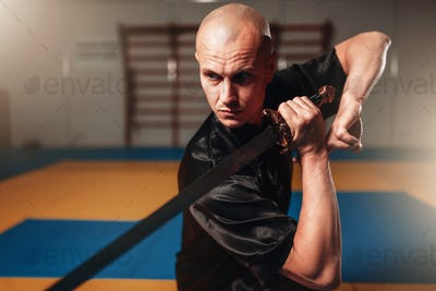 Wushu master with blade in action, martial arts
