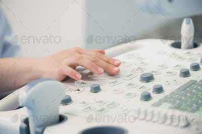 Hands on an ultrasound machine at modern clinic