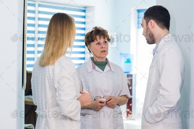Mature doctor discussing with nurses in a hallway hospital. Doctor discussing patient case status