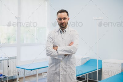 Portrait of a serious confident male doctor standing with arms crossed at medical office