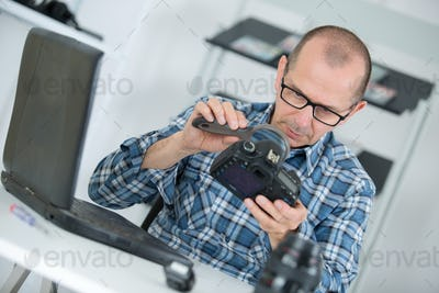 Repairman looking at camera through magnifying glass