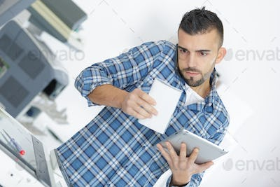 Repairman holding phone between chin and shoulder