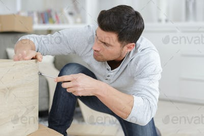 man assembling furniture at home on the floor