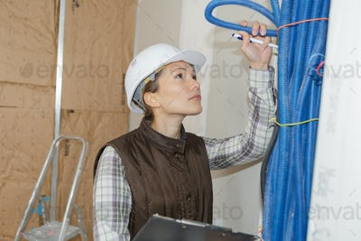 woman builder fixing heating system