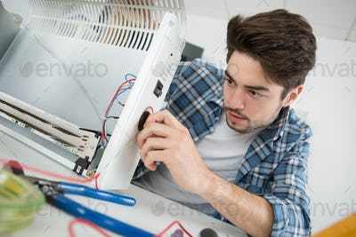young male plumber examining electric heater