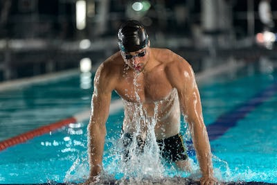 Male swimmer lifting himself out