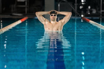 Male swimmer standing in pool