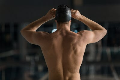 Rear view of a male swimmer adjusting his goggles