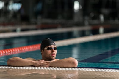 Male swimmer wearing goggles and swimming cap resting