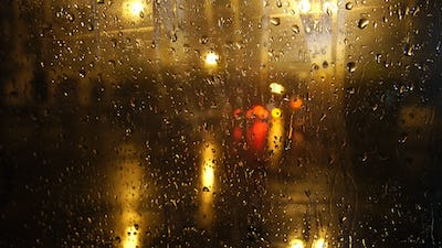 View of the night street through wet glass