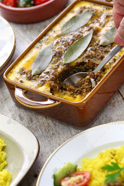 bobotie is a curry flavored meatloaf with baked egg on top.