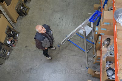 Man looking up at shelves in warehouse