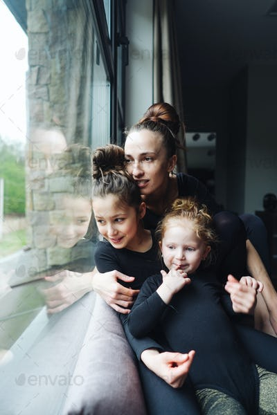 Mom and two daughters together at the window