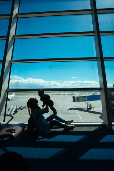 Little boy and his mother sitting in an airport