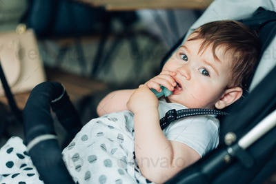 Little boy sitting in a baby carriage