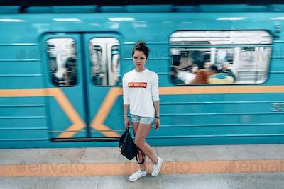 Beautiful young girl posing on metro station
