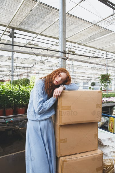 Girl lying on boxes in greenhouse