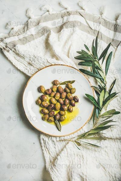 Pickled green olives in olive oil on white ceramic plate