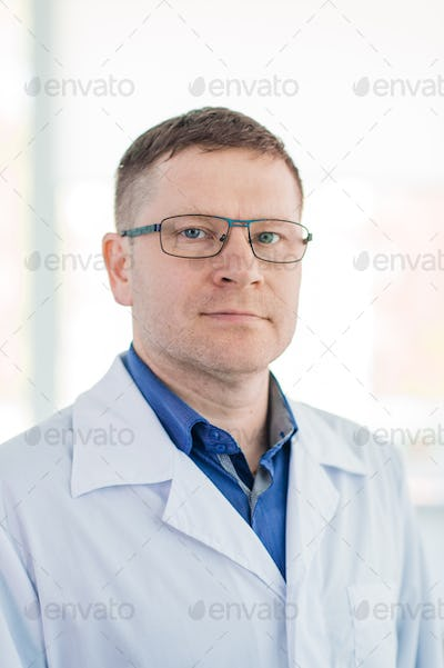 Portrait of confident mature male surgeon standing arms crossed in hospital
