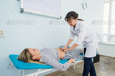 Doctor checking the stomach of one of her patients