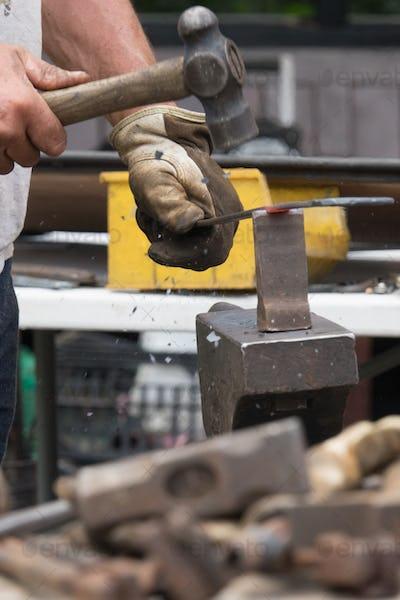 A blacksmith hammering hot iron