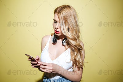Young blonde woman wearing headphones and using mobile phone