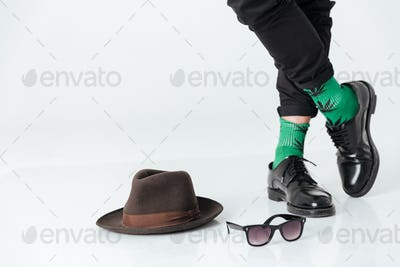 Cropped image  man standing on floor near hat and sunglasses