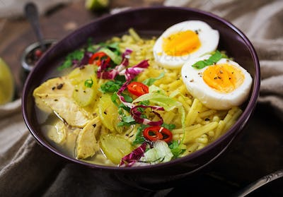 Noodle soup with chicken, celery and egg in a bowl on a old wooden background.